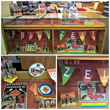 Colorful sales counter featuring banners, printed ads, spices, and a summer grilling theme